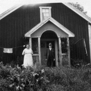 Portrait of Henry Segerstrom's grandparents Berta and Charles John (C.J.) Segerstrom in front of their home in Jarnberget, Sweden.