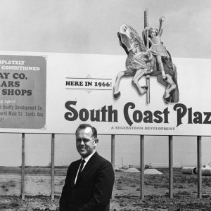 Henry Segerstrom poses in front of a South Coast Plaza sign